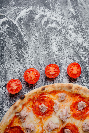 Pizza pepperoni. This picture is perfect for you to design your restaurant menus. Visit my page. decorated with sliced tomatoes and mushrooms,  black background with flour, Top view. Banner, close-up, copy space Reklamní fotografie - 124866934
