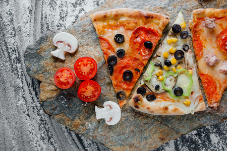 Set pizza. Italian cuisine. decorated with sliced tomatoes and mushrooms, sliced peppers,  black background on  stone with flour, Top view. Banner, close-up, copy-space Reklamní fotografie - 124866943