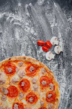 Pizza with Chicken meat, Mozzarella cheese, pepperoni, tomato, vegetables, salami. Italian pizza, decorated with sliced tomatoes and mushrooms, black background with flour, Top view. Banner, close-up, copy space Reklamní fotografie - 124866947