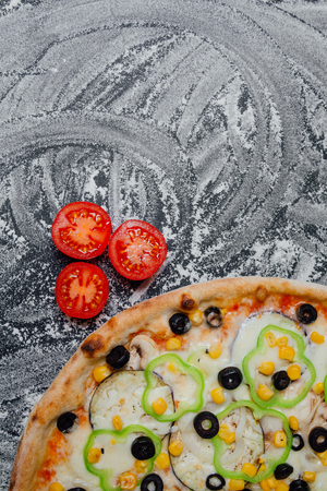 Pizza with olives, tomato cherry, onion.  Fresh italian pizza. Pizza with cheese ham peppers olives board, black background with flour, sliced peppers, Top view. Banner, close-up, copy space