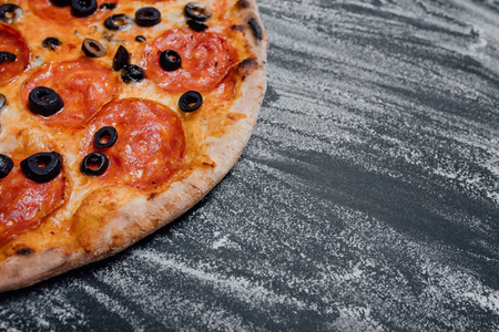 Tasty pepperoni pizza and cooking ingredients tomatoes, black background with flour, Top view. Banner, close-up, copy space for text