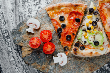 different pizza set for menu. Pizza with salami, pizza with mozzarella, salami, sausages, pizza four cheese decorated with sliced tomatoes and mushrooms, sliced peppers,  black background on  stone with flour, Top view. Banner, close-up, copy-space Reklamní fotografie - 124866987