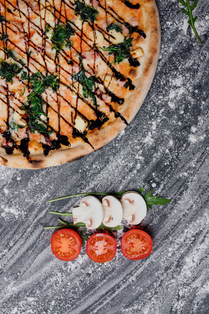 Tasty seafood pizza with cherries, decorated with sliced tomatoes and mushrooms, black background with flour, Top view. Banner, close-up, copy space