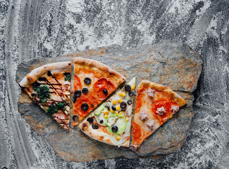 slices of different pizza, pepperoni,  black background on  stone with flour, sliced peppers,  Top view. Banner, close-up, copy-space Reklamní fotografie - 124866989