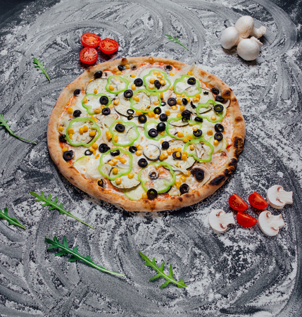 Pizza with ham, yellow and red pepper black olives and fresh basil. Italian pizza. Homemade food. Symbolic image. Concept for a tasty and healthy meal. black background with flour, Top view. Banner, close-up, copy space