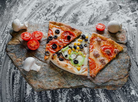 slices of different pizza, pepperoni, decorated with sliced tomatoes and mushrooms, sliced peppers,  black background on  stone with flour, Top view. Banner, close-up, copy-space