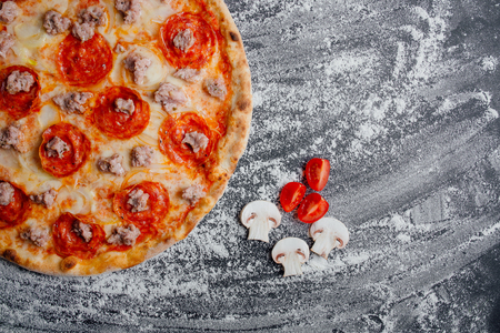 Homemade pizza with tomatoes, mozzarella, black background with flour, decorated with sliced tomatoes and mushrooms, decorated with sliced tomatoes and mushrooms, Top view. Banner, close-up, copy space Reklamní fotografie - 124867021