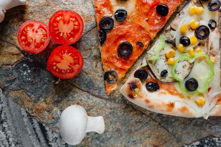 Compound pizza from slices of different pizza,  decorated with sliced tomatoes and mushrooms, sliced peppers,  black background on  stone with flour, Top view. Banner, close-up, copy-space