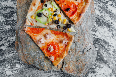 slices of different pizza, pepperoni,  black background on  stone with flour, sliced peppers,  Top view. Banner, close-up, copy-space Reklamní fotografie - 124867031