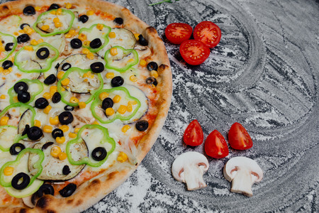 Pizza with ham, black olives, cherry tomatoes, spices and fresh basil. Italian pizza. Home made food. Concept for a tasty and hearty meal. , black background with flour, sliced peppers, Top view. Banner, close-up, copy space