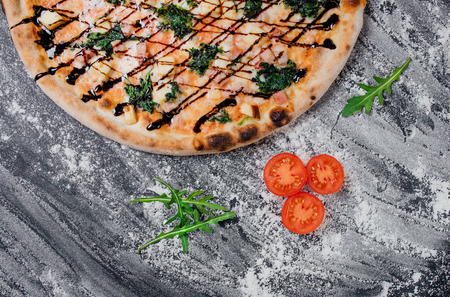 Delicious pizza with tomatoes and fresh basil , decorated with sliced tomatoes and mushrooms, black background with flour, Top view. Banner, close-up, copy space Reklamní fotografie