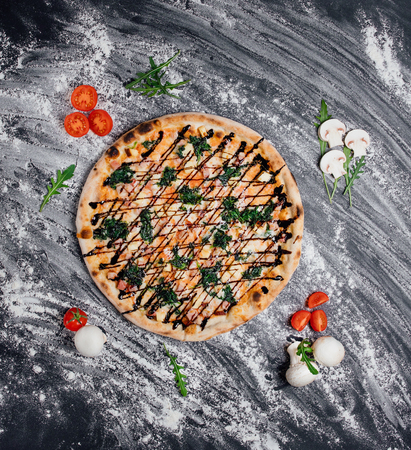 Hot meat pizza with salami, cream cheese Feta and Tomato Slices decorated with fresh greens, black background with flour, Top view. Banner, close-up, copy space