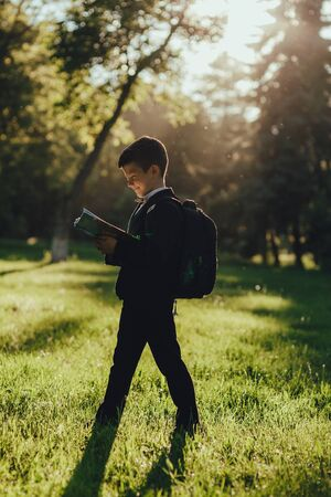 beautiful schoolboy portrait reads the book, is happy after school, profile view, outdoor, at sunset Standard-Bild