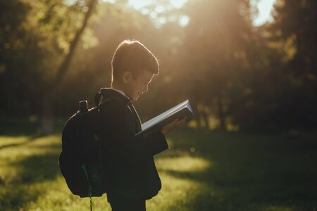 schoolboy learns from the book, dressed in school uniform, with a schoolbag in the park, profile view, outdoor, at sunset Standard-Bild