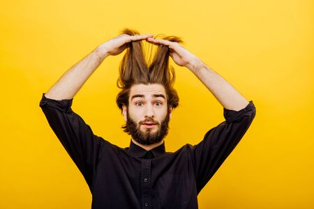 man pulls his hair up, raises long hair up, is surprised, I look healthy. isolated on yellow background, facial expression positive Фото со стока