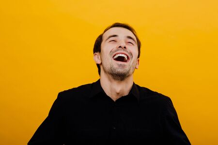 young man smiles, in his black shirt, isolated yellow background, studio, ecstasy and joy, positive emotion facial expression