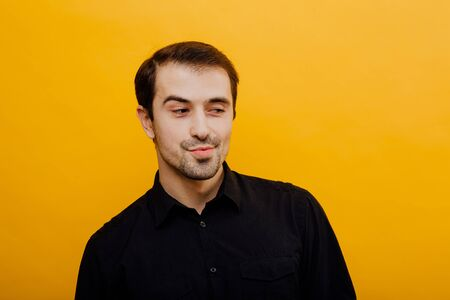 young man, looks with interest, isolated on yellow background, studio