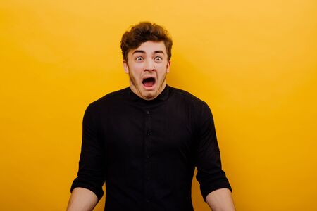 Portrait of a guy who screams in a panic, screaming with fear, makes a loud cry as he is amazed and very scared,  isolated on a yellow background