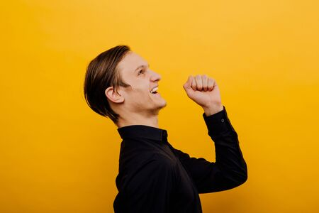 male winner, young and beautiful, enjoy winnings and pick up mines up,  positive human emotion facial expression yellow background, studio, isolated Reklamní fotografie