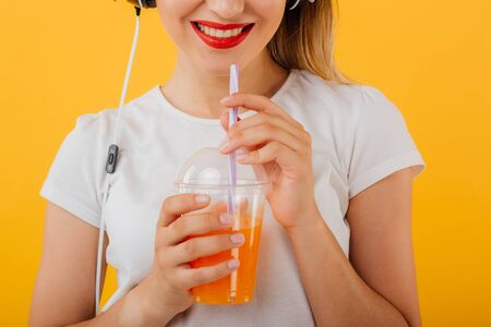 Close up.  beautiful young girl's red lips, holds your plastic cup with juice dressed in a white shirt,  positive facial emotion isolated on a yellow background Stockfoto