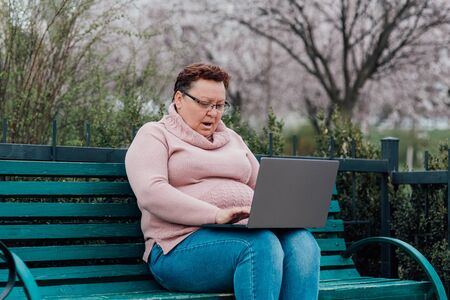 mature woman in glasses using laptop, is scared, a saw which also should not see, dressed in a pink sweater and in jeans sitting on a chair in the park