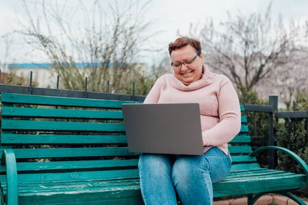 Satisfied middle aged woman using laptop messaging with friend sharing funny videos and news communicating online, dressed in a pink sweater and in jeans sitting on a chair in the park Stockfoto