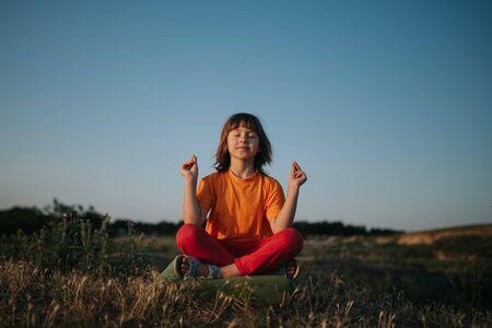Happy little girl meditates, yoga, dressed in orange shirt, outdoors