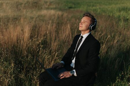 happy young man with headphones on listening to music on field head, sat down, using laptop, eyes closed, outdoor Imagens
