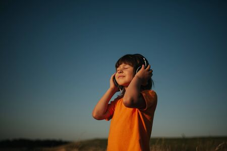 little girl listens to music in her head, in the field, holds her eyes closed, dressed in orange shirt, outdoors, sky background