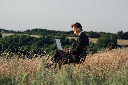 blogger uses notebook, in the field, sitting on chair, in suit, working on laptop, profile view, outdoor