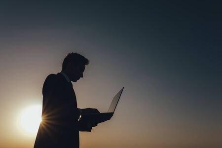 young businessman using laptop, Internet and social network concept, at sunset, copy space, profile view, sky background, outdoor Reklamní fotografie