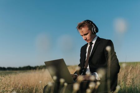 young businessman with headphones using video chatting, in field, sitting on chair, outdoor