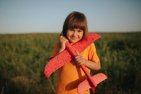 girl is holding red plane, dressed in yellow shirt, look at the camera, outdoors
