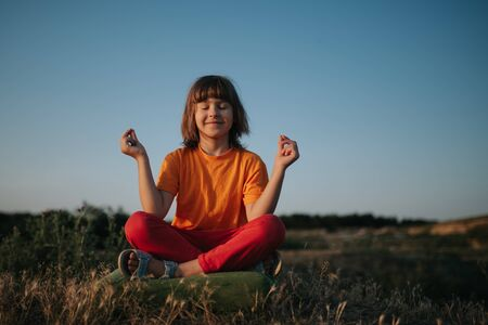 little girl deals with yoga, dressed in orange shirt, at sunset, outdoors