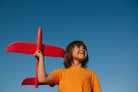 Beautiful kid holding in hands a red toy airplane on a background of blue sky, outdoors, sky background, copy space
