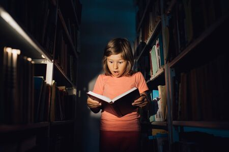 little girl reads the book, is amazed. holds your book, learns in the library, indoors