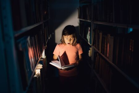 little girl reads the book, is scared, has open mouth. holds a book in his hand, learns in the library, indoors