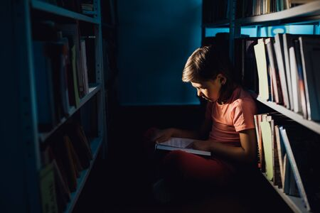 little girl reading a book in the library, sitting down, profile view, indoors