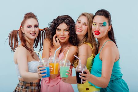 four happy young girls with unusual hairstyle and make-up, holding plastic juice cups, looking at the camera isolated blue background, positive facial emotions, copy space Reklamní fotografie