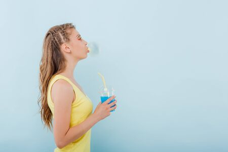 close up. young girl chewing gum bubbles, has plastic cup with juice in hand, dressed in yellow shirt, side view, positive facial emotions, isolated on blue background, copy space