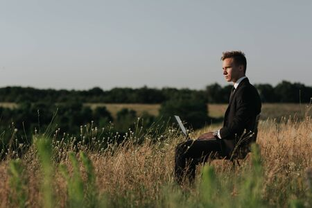 Young businessman on meadow,  sitting in the chair, using a laptop, outdoor, profile view Reklamní fotografie