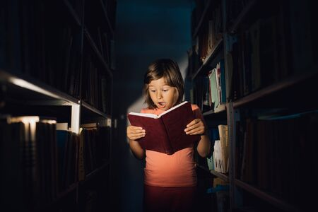 little girl reads the book, is scared. holds your book, learns in the library, indoors
