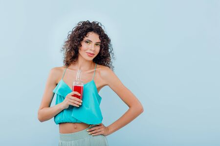 Young beautiful lady smiles has the drink bottle in her hand, with curly hair, dressed in blue shirt, looks in the camera positive facial emotions, isolated on blue background, copy space Reklamní fotografie