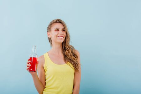 young girl smiles amazefully, has the drink bottle in her hand and looks sideways, positive facial emotions, idressed in yellow shirt solated on blue background, copy space