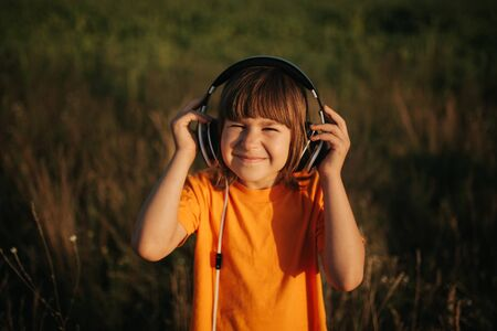 little girl listens to music in her head to nature, outdoors