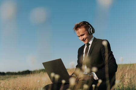 young happy businessman with headphones using video chatting, in field, sitting on chair, outdoor Reklamní fotografie