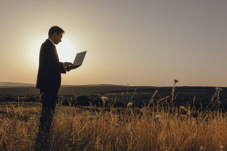 young man using laptop, Internet and social network concept, at sunset, copy space, profile view, outdoor