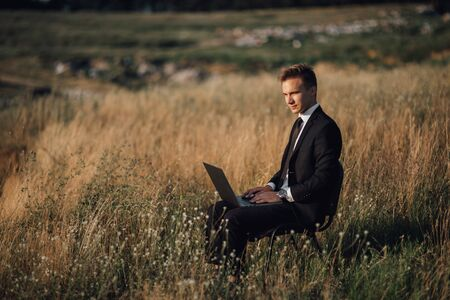 young businessman with laptop in the field, sat down, in suit, look sideways, outdoor