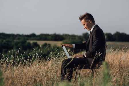 young businessman with laptop in the field, outdoor, profile view