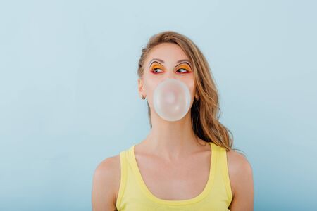 close up. young girl chewing gum bubbles, dressed in yellow shirt, positive facial emotions, isolated on blue background, copy space